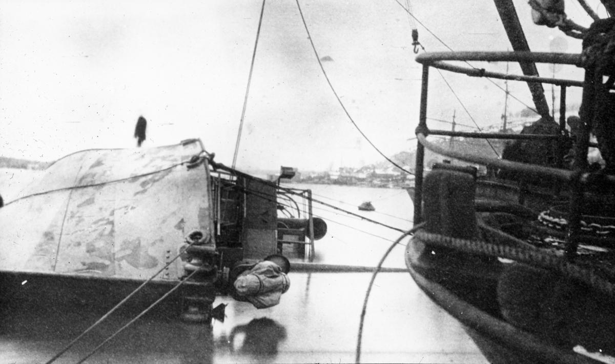Havarert skute trukket mot land av annet fartøy. Kystlandskap.