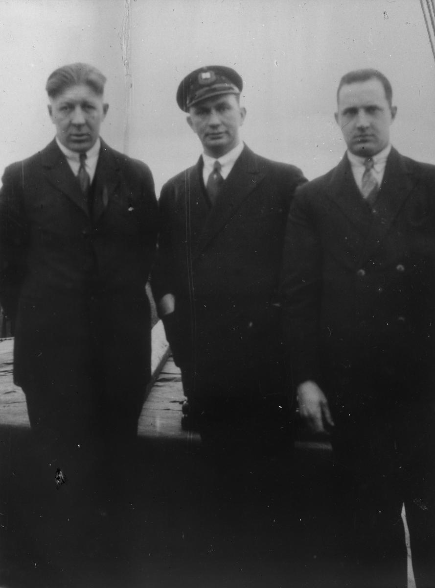 Tre menn ombord på et fartøy.