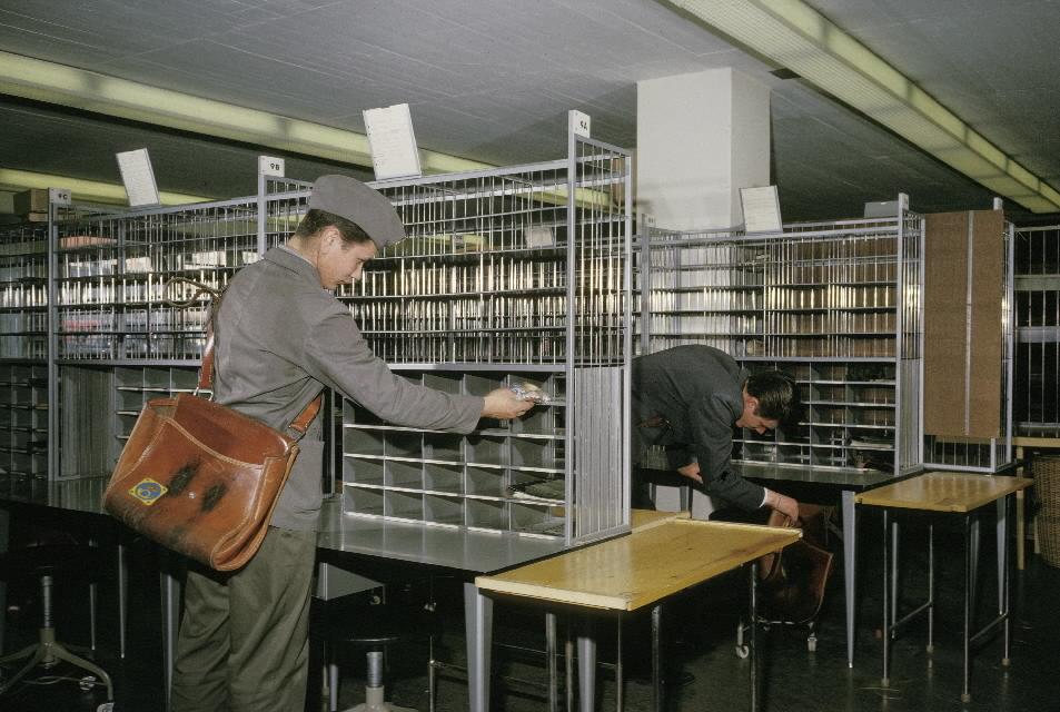 Seriebild 4. Brevbärarsalen kl 0600 då personalen anländer till sitt lag. En av postiljonerna lägger ett paket med smörgåsar i avsett fack i bordsuppsatsen. Situationen är arrangerad.