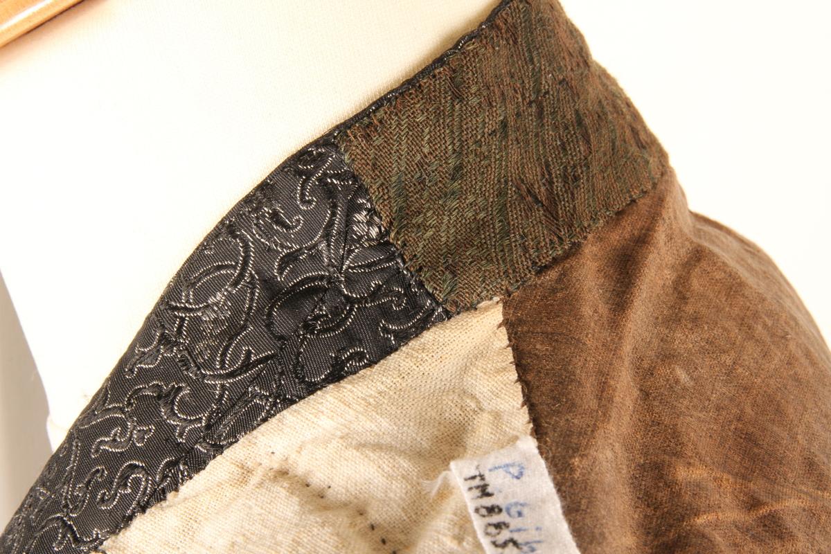 Enkeltkneppet silkevest i svart silkebrokade. Silkebrokaden har innvevde sølvtråder som danner mønsteret. Rygge er i brunt linstoff, og har snøring midt bak. Vesten er foret med hvitt linstoff. Hele vesten er sydd for hånd, i hovedsak med lintråd.