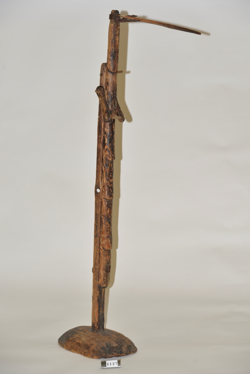 Ljushållare där tjärstickan är instucken i en höj-och sänkbar ställning av trä.  Ljuskäringen har använts i givarens föräldrahem.