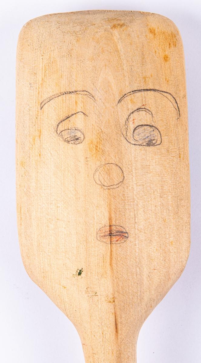 """Acc.kat: Slev. Trä, omålad. Raka kanter på tre sidor av skedskålen. På baksidan ett ritat ansikte i blyerts och färgpenna. Skaftet märkt """"3421/-50""""."""