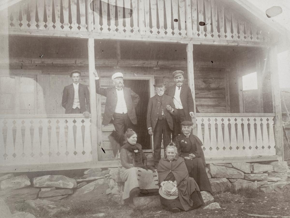 Gruppeportrett av 7 mennesker på trappa utenfor et hus. Noen identifisert som familien Eng.