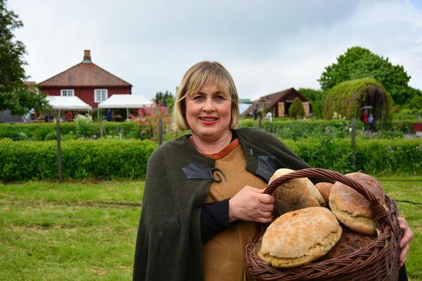 Kvinne med kurv full av runde brød over armen.. Foto/Photo