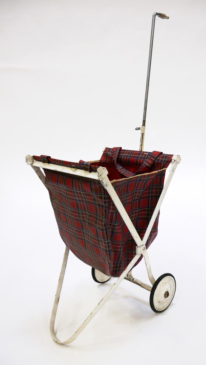 """Äldre exemplar av shoppingväska, så kallad """"Dra maten"""". Vitmålad hopfällbar metallställning med löstagbar väska i rutig plastbehandlad textil.  Har tillhört Karin Lundin som någon gång under 1900-talets andra hälft fick överta väskan efter en vännina som inte längre kunde göra egna inköp på grund av ålder. Lundin använde den dock aldrig då hon inte ville synas på stan med väskan."""