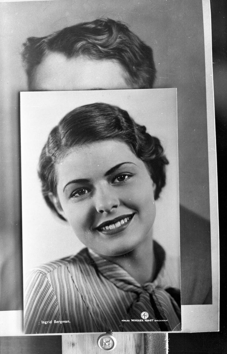 Foto (reprofoto) av foto av skådespelerskan Ingrid Bergman (1915-1982). Hon var en tid elev vid Klosters röstskola, Alvesta. Ateljéfoto. Bakom sitter ett skymt fotografi av hennes far. Vid sjön Salen i sin barndomstrakt Alvesta byggde Karl Nygren-Kloster 1914 en 4-vånings träbyggnad, som kom att inrymma hans livsverk, Klosters röstskola, där många av landets sångare och skådespelare grundlagt eller utvecklat sitt kunnande. N ledde kurser vid Kloster till 1936, då sänkningen av Salen orsakat så stora sanitära problem att undervisningen måste flyttas; den fortsattes vid Viggbyholms folkhögskola norr om Sthlm. 1942 övertogs verksamheten på Kloster av brorsönerna Åke, Bertil och Olle Nygren, vilka bedrev den i samma byggnad fram till 1 april 1952, då allt brann ner till följd av ett pyromandåd.
