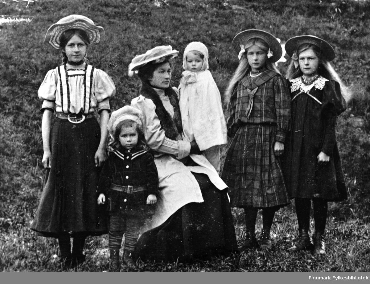 Portrett fra familien Noodt. Mor, Hanna Noodt, fotografert med sønnene Håkon og Leif. Med på bildet er også Eilert Marcus Noodts tre dødre, Elna, Aslaug og Gudrun, fra hannes første ekteskap.  Hanna Noodt var gift med Eilert.