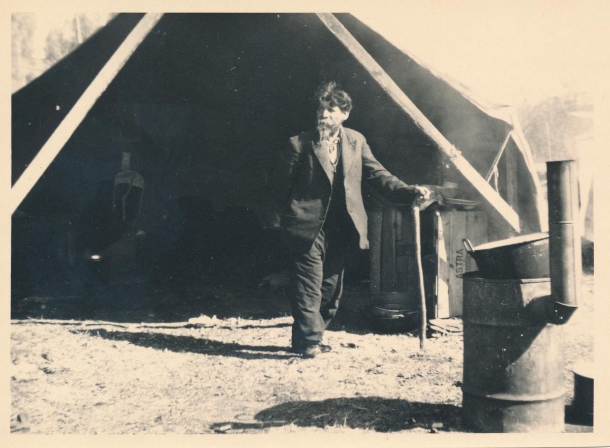 En äldre man stöder sig mot en käpp, stående framför ett tält. Bilden är troligen tagen i samband med marknaden i Torsby.