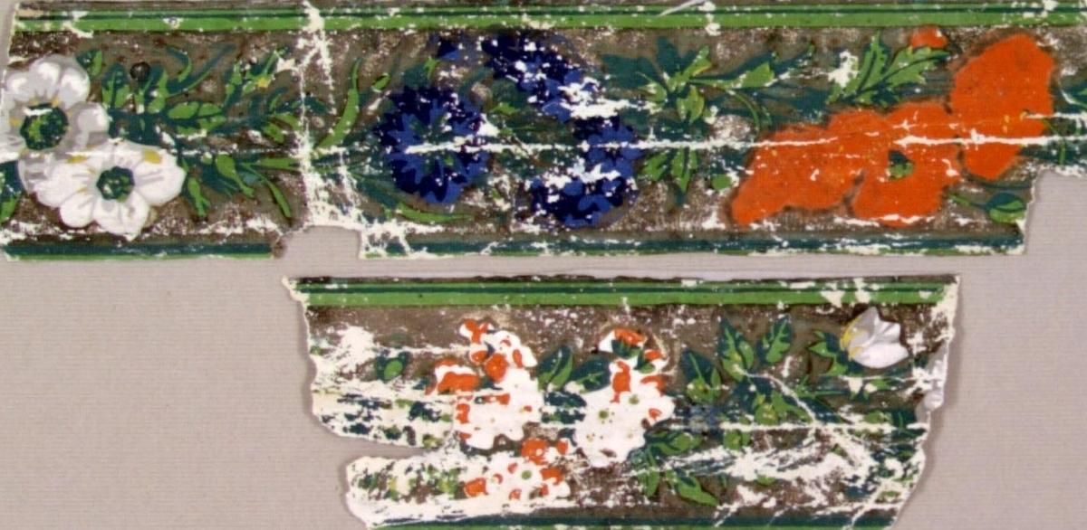 /Brev finnes/  Blomranka bestående av vallmo, blåklint mm. Tryck i orange samt i två gröna och två blå nyanser på en ljusgrå bakgrund.