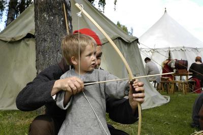 Bueskyting er populær middelalderaktivitet, her err det en liten gutt som får hjelp av en voksen mann til å spenne buen, begge har på seg enkle middelalderklær, og det står middelaldertelt i bakgrunnen.