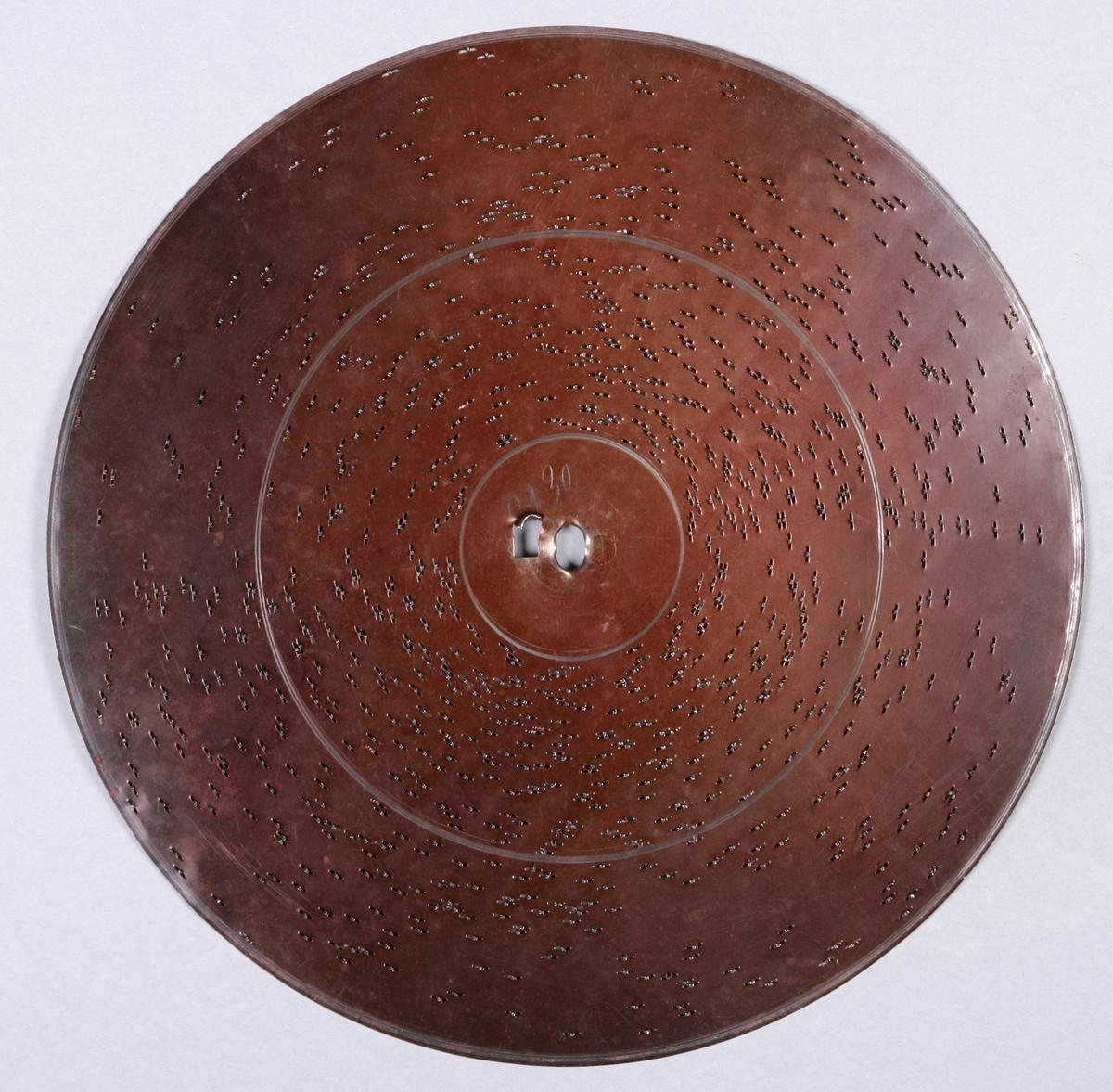 """Perfortert metallplate med pigger på underside. Programmert musikk for platespilledåse. 86-spor, Ø 30 cm. Drivsystem: Sentrumshull med kvadratisk """"satellithull"""" ved siden (7x5 mm).  Sentrumhull, diameter: 8 mm  Avstand mellom 10 spor: ca 13 mm. Avstand sentrumsaksling – første spor:  33,8 mm Total bredde spor:  110,4 mm"""