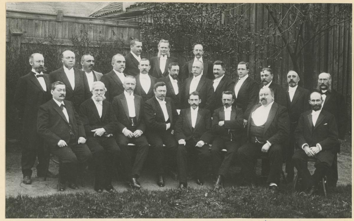 Trolig fra Moss Handelsstands Forening sitt 20-årsjubileum i 1907, fotografert i Moss Hotell sin hage ca. 1901-7. Personene på bildet er født ca. 1850-60.  1. rekke, fra venstre: Joh. Anthoniussen (konsul), Jørgen Haslum, D. E. Martens (banksjef), Kristian A. Olsen (lensmann), Johan Haslum (kontorsjef), Einar Bugge (grosserer), Christen Sandberg (konsul), Hans Haslum (skipsreder). 2. rekke, fra venstre: Kase (kaptein), Hoel (bryggerieier), Paul Alfred Berg (sakfører), Helle Juell Beck (samlagsbestyrer), Chr. F. Flemming (kjøpmann), Chr. Strøm Sandberg (kjøpmann), Johannes D. Fürst (politimester), Hans Gutzeit (disponent), Sigurd Bang (kjøpmann), Otto Rønneberg (havnefogd), Emil Christophersen (murmester, Melløs), Johan Jensen (fullmektig). 3. rekke fra venstre: Marius Christophersen (kjøpmann), O. Simonsen (barbermester), Johan L. Henriksen (konsul).