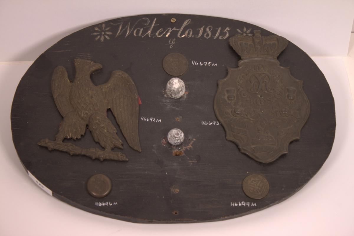 Hul engelsk uniformsknapp i messing 22.5mm stor. Motiv: Kongens monogram (GR) omgitt av ordene ROYAL ENGINEERS i oval under en krone, se foto. På baksiden påloddet et øye i kobber. Gjenstanden er, sammen med andre gjenstander funnet på slagmarken ved Waterlo, montert på en oval sortmalt treplate med påskrift i hvit maling: *Waterlo 1815* 18/6.