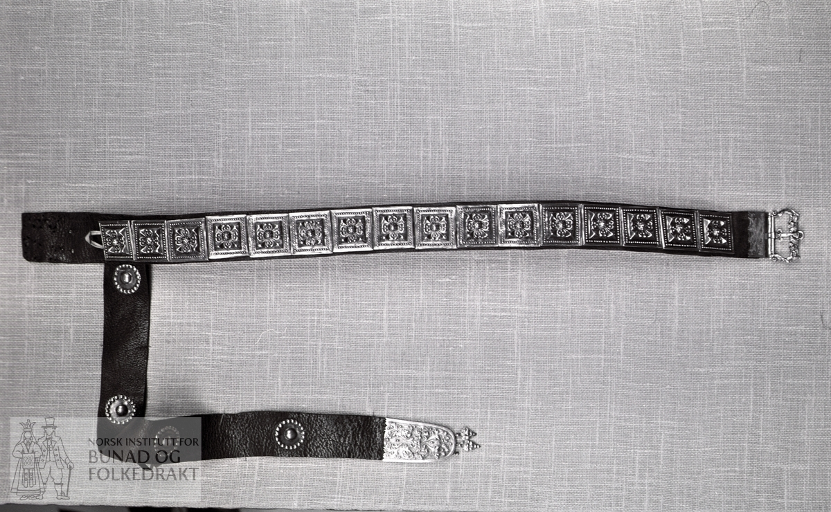 """Nordhordlandsmessa 1974 nr. 125.  Forgylt metall.  """"Duppsko"""" nederst på fangbandet.  Inngravert ROS GKD 1717 3 Vej 26 Lod Kost = 23 (se reg.kort).  Spenne av messing, støpt.  Stølene 4,5 x 4,5 cm.  Bredde på lærbelte:  5 cm, lengde:  85 cm.  Fangband bredde:  5,3 cm øverst 4,5 cm, bredde nederst ved Duppsko.  Duppsko:  Høyde:  8,1 cm 4 """"skjold"""" på fangbandet diam.:  3,3 cm."""