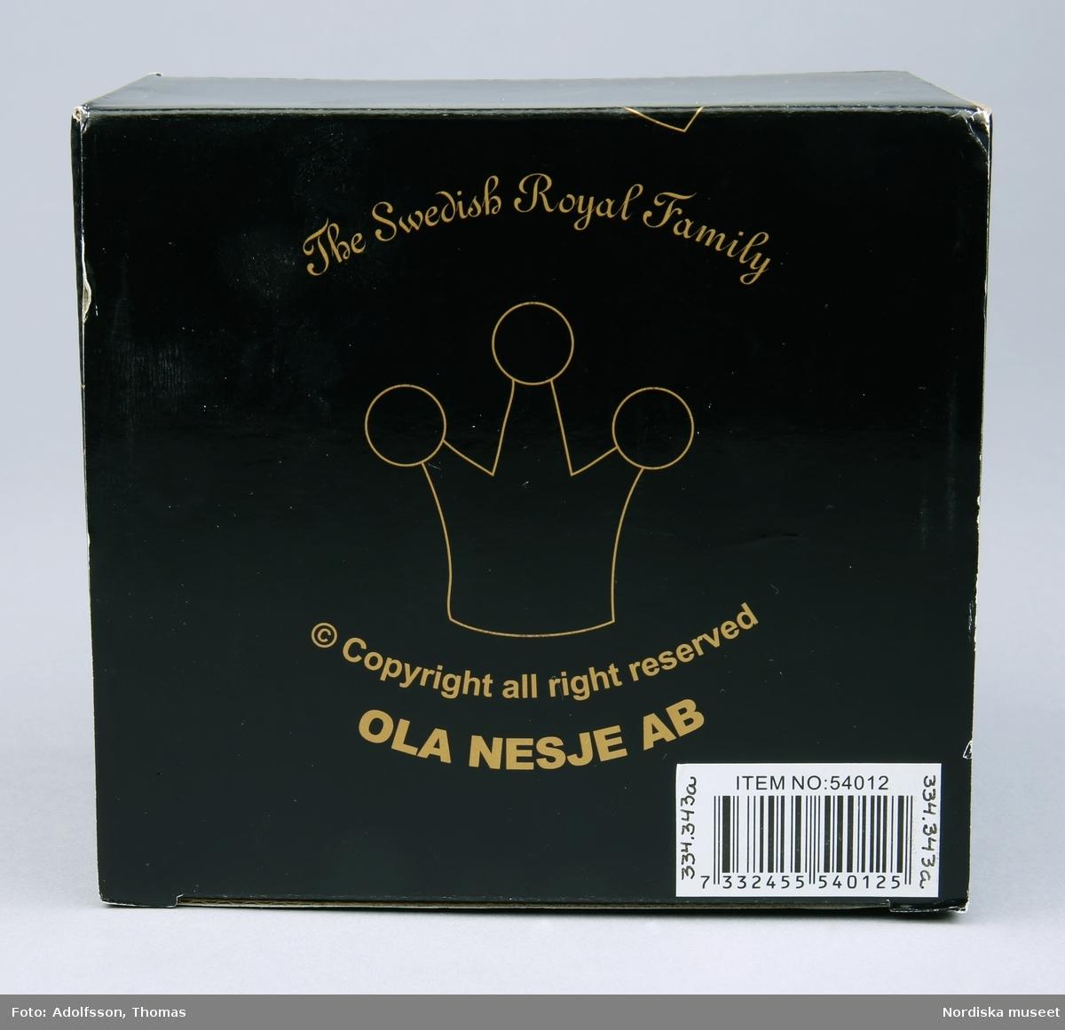 """a) Förpackning/kartong  av svart papp, dekor och text i guldfärg. b) Löst påskjutslock av transparent plast. Inuti asken c) lös insats av papp med urtag för muggen.  Text på kartongen; """"The Swedish Royal Family"""", """" © Copyright all right reserved OLA NESJE AB""""  I botten etikett med strckkod/EAN-kod 7332455540125 och text """"ITEM NO: 54012"""" Prislapp på påskjutslocket """"69:  Anm. tejprester på ena sidan av påskjutslocket. /Johanna Krumline 2011"""