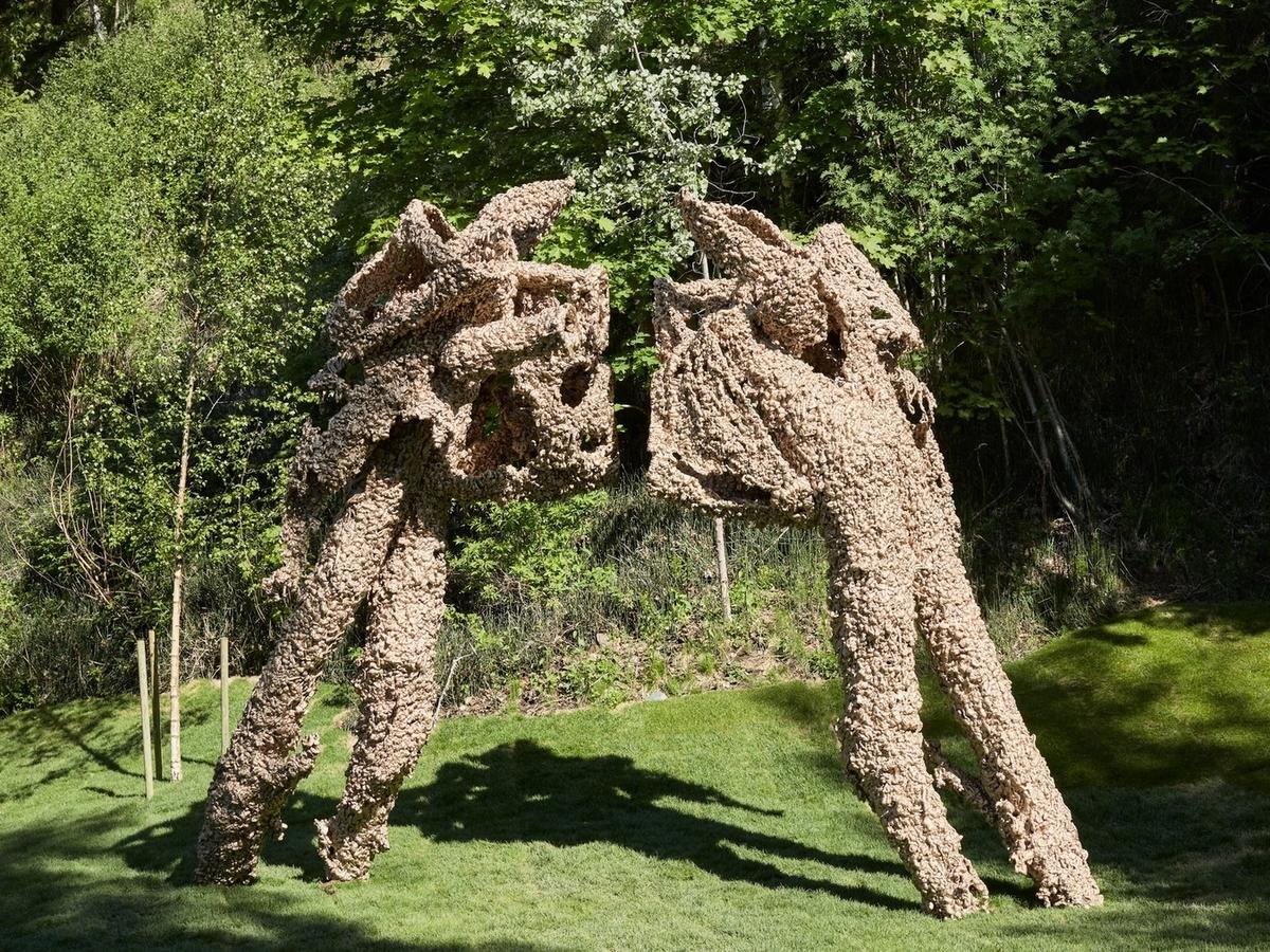 """To """"figurer"""", begge på ca. 450 cm, som står mot hverandre i en type """"face off"""". Abstrakte former. Ujevn overflate på begge figurene."""