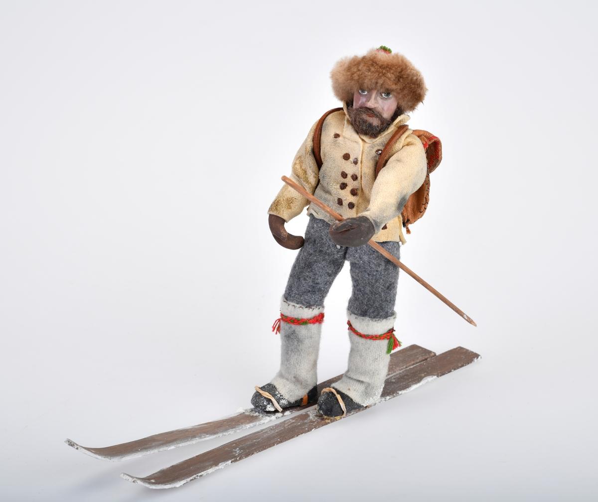 Liten mannsfigur med ryggsekk, ski på beina og en langstav/skistav i hånden.