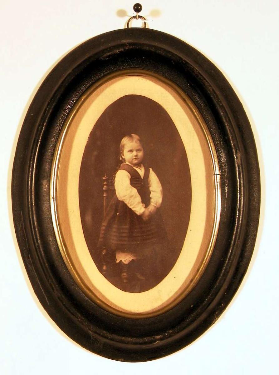 Portrettfotografi av en liten pike stående på stol ikledd hvit bluse, mørk kjole med vest, mammelukker og støvler.