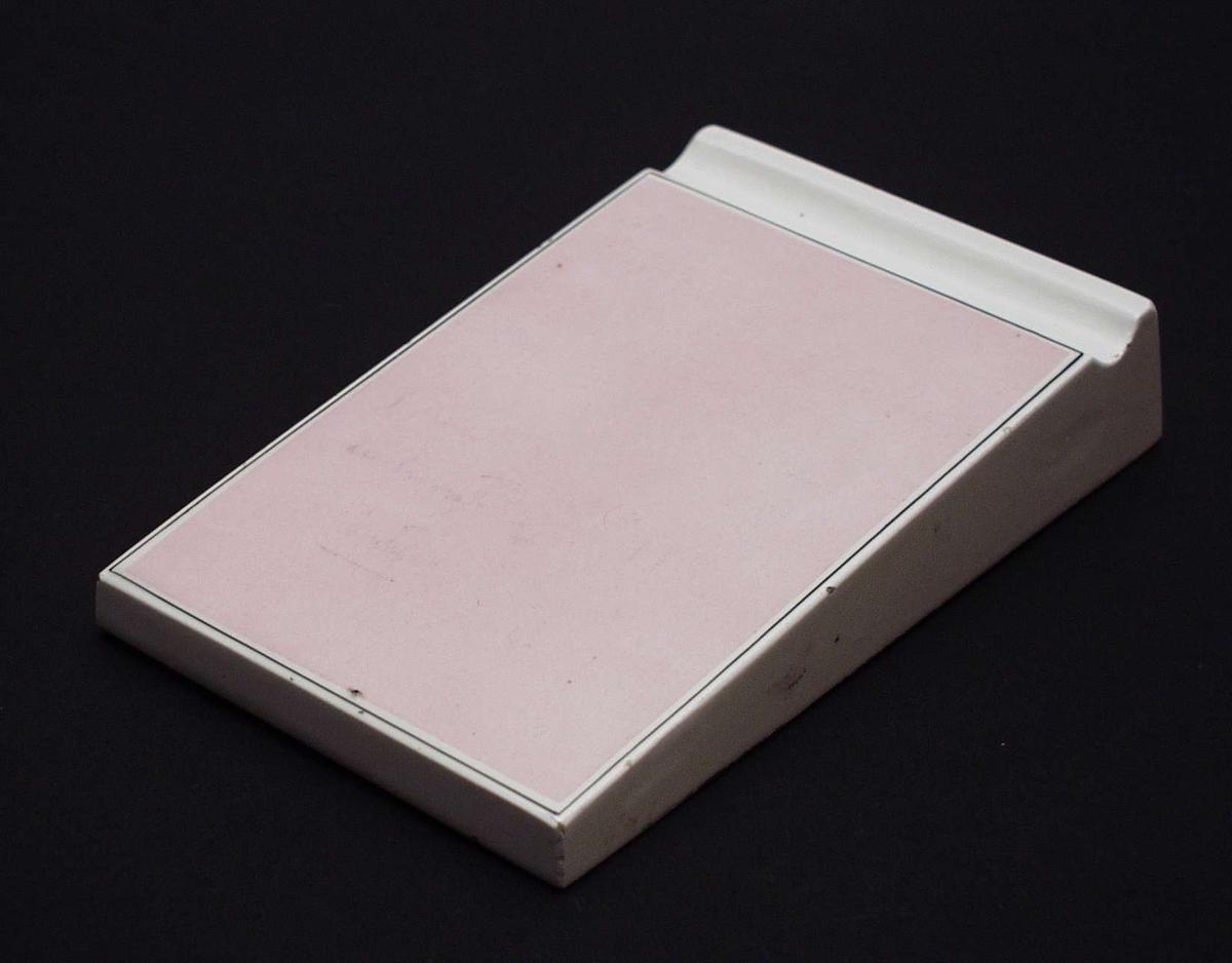 Notisblokk med buet kant til blyant. Den er laget i hvit keramikk med lyserødt skrivefelt.