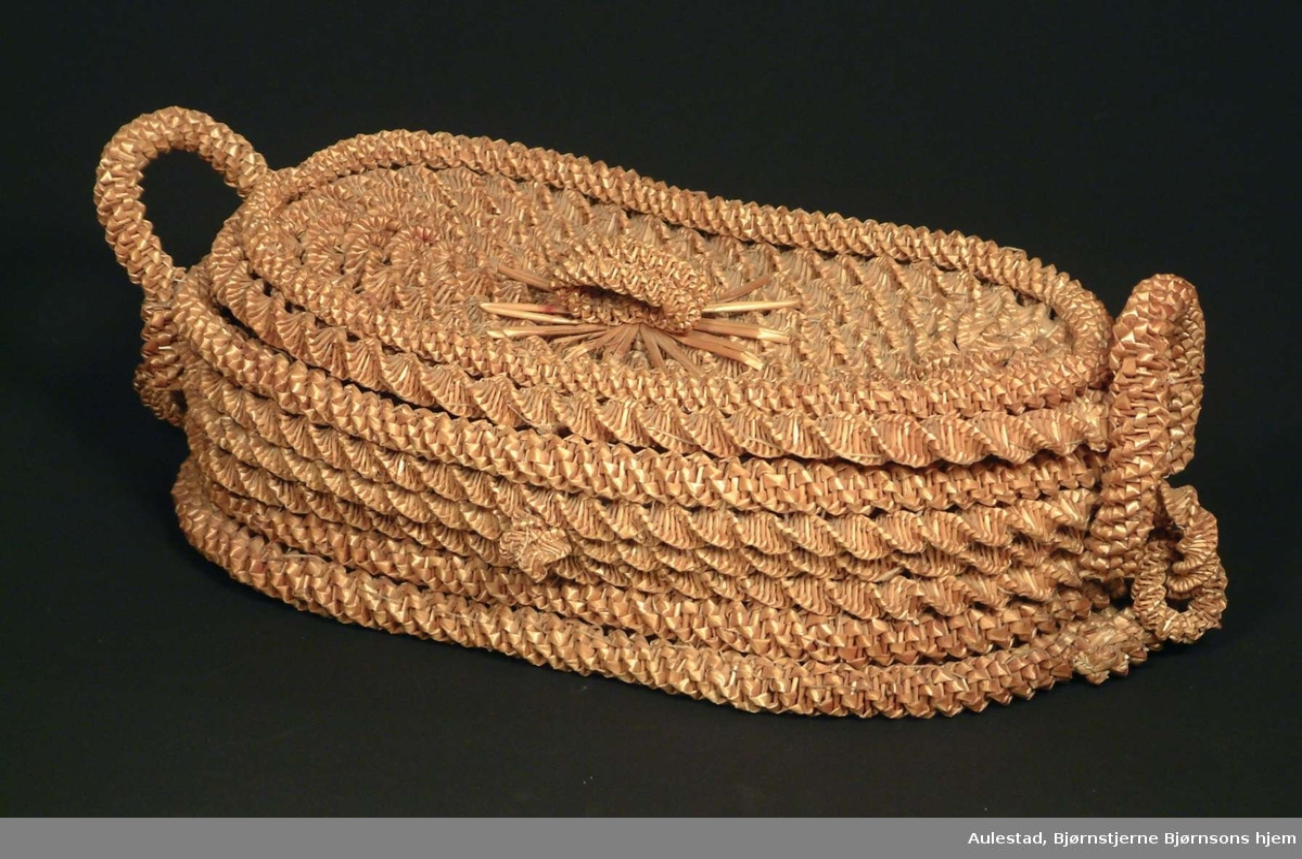 Oval kurv med lokk og håndtak flettet av strå.