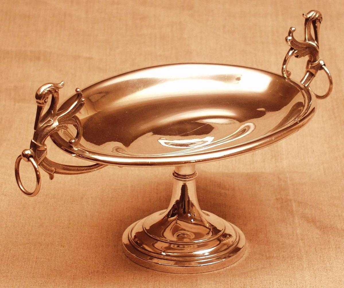 Ovalt, oppadbøyet, 10 cm. h. rund stett som smalner oppad, på hver smalende av fatet er fantasiknotter forsynt m. løsringer.