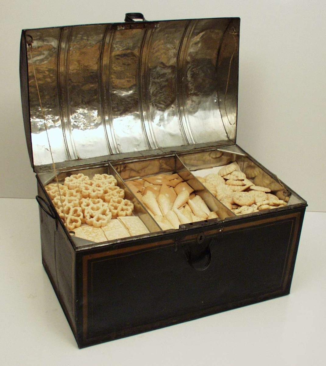 Buet lokk. Tilsammen fire håndtak på lokk og koffert. Kofferten er låsbar. Innvendig er den tredelt.