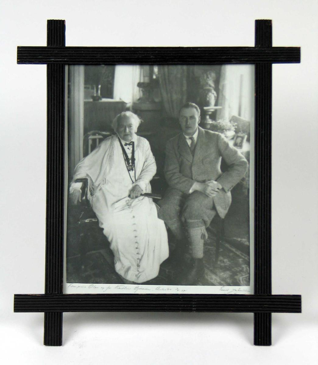 Eldre kvinne i lang hvit kjole sittende til venstre, ung mann i tweedjakke, nikkers og strikkede strømper med bånd til høyre.