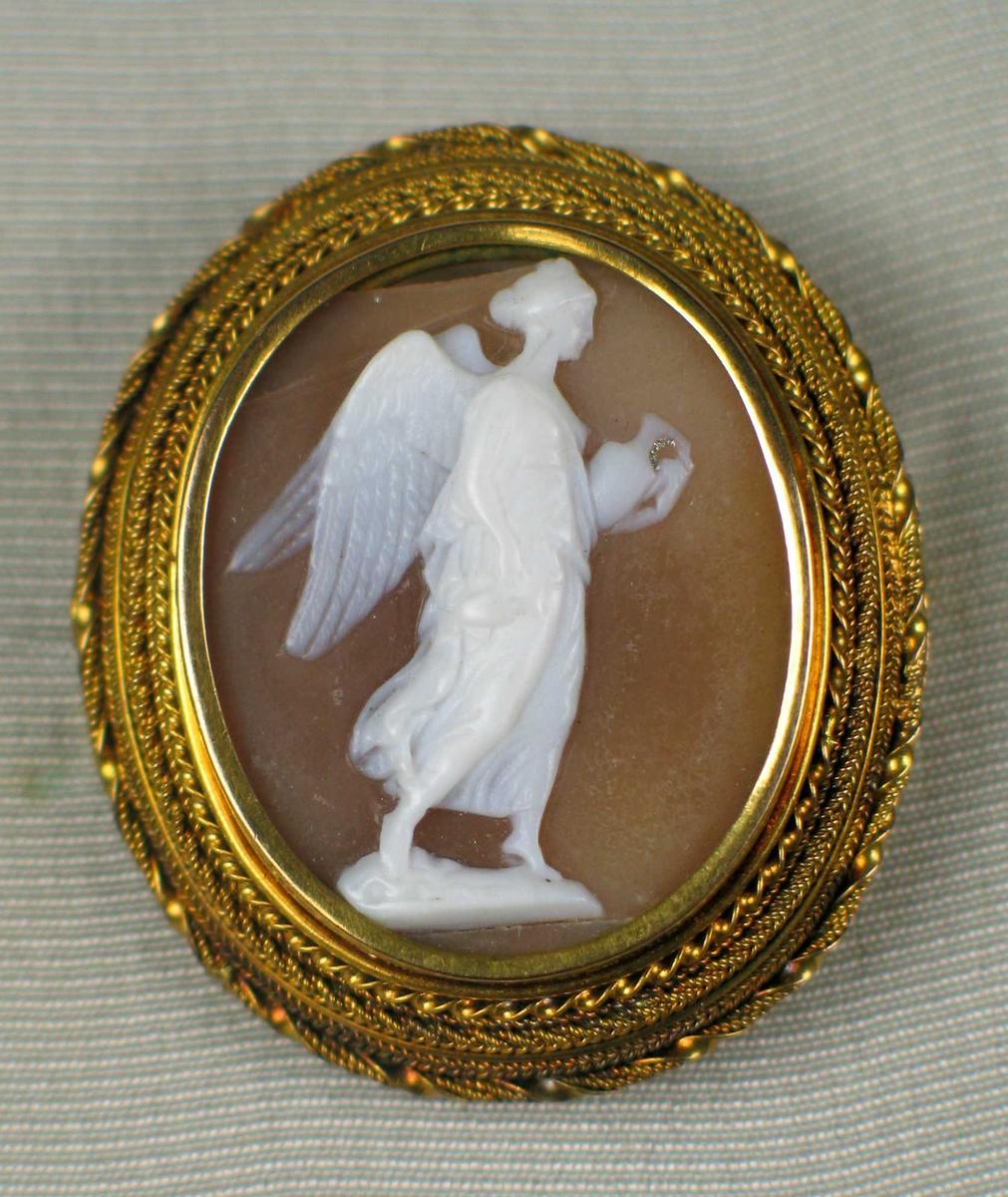 Kamè/medaljong innfattet gull som består av sirlige filigransborder. I midten en utskåret hvit engel som bærer en krukke.