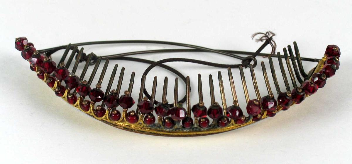 Hårpynt i diademfasong med tinder rundt. Bøylen er i forgylt metall dekorert med margeritter og øverst to rader rød steiner. Metallstenger og strikk bak.