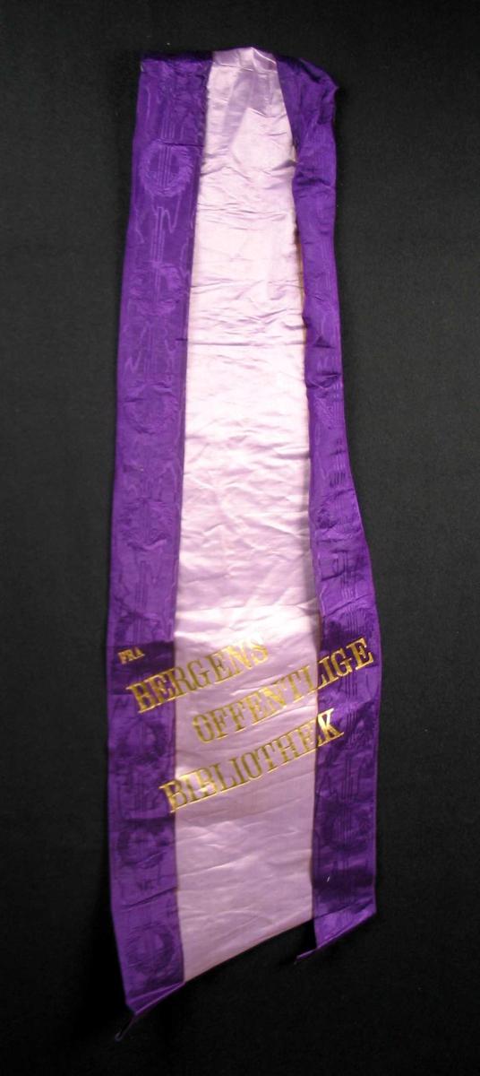 Begravelsessløyfe i lilla silke med skrift i gull.