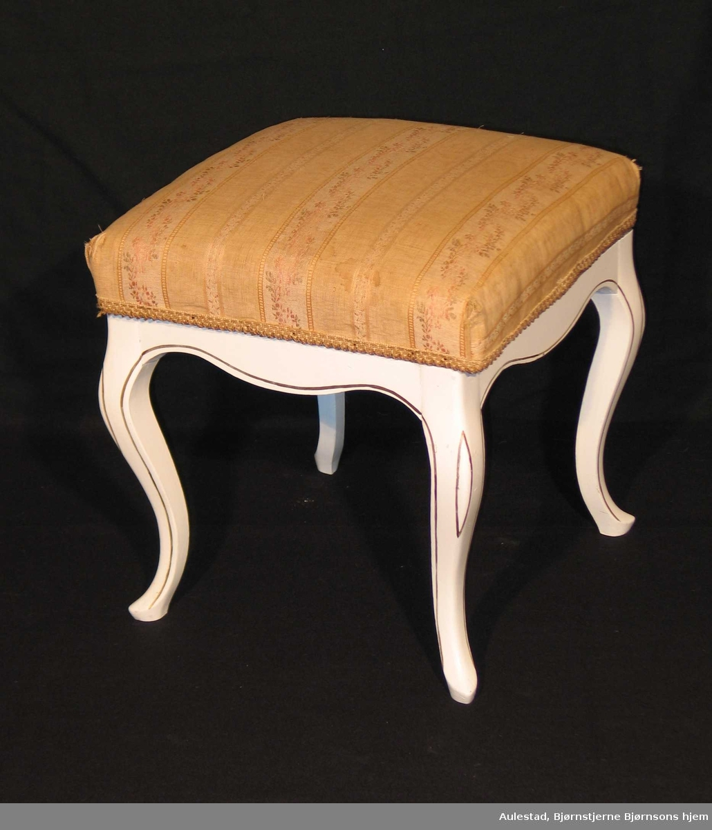 Hvitmalt krakk i bjørk med en enkel bronselinje malt langs kantene. Stoppet sete trukket om i brokadestoff (skaffet av Dagny.) Svungne ben.