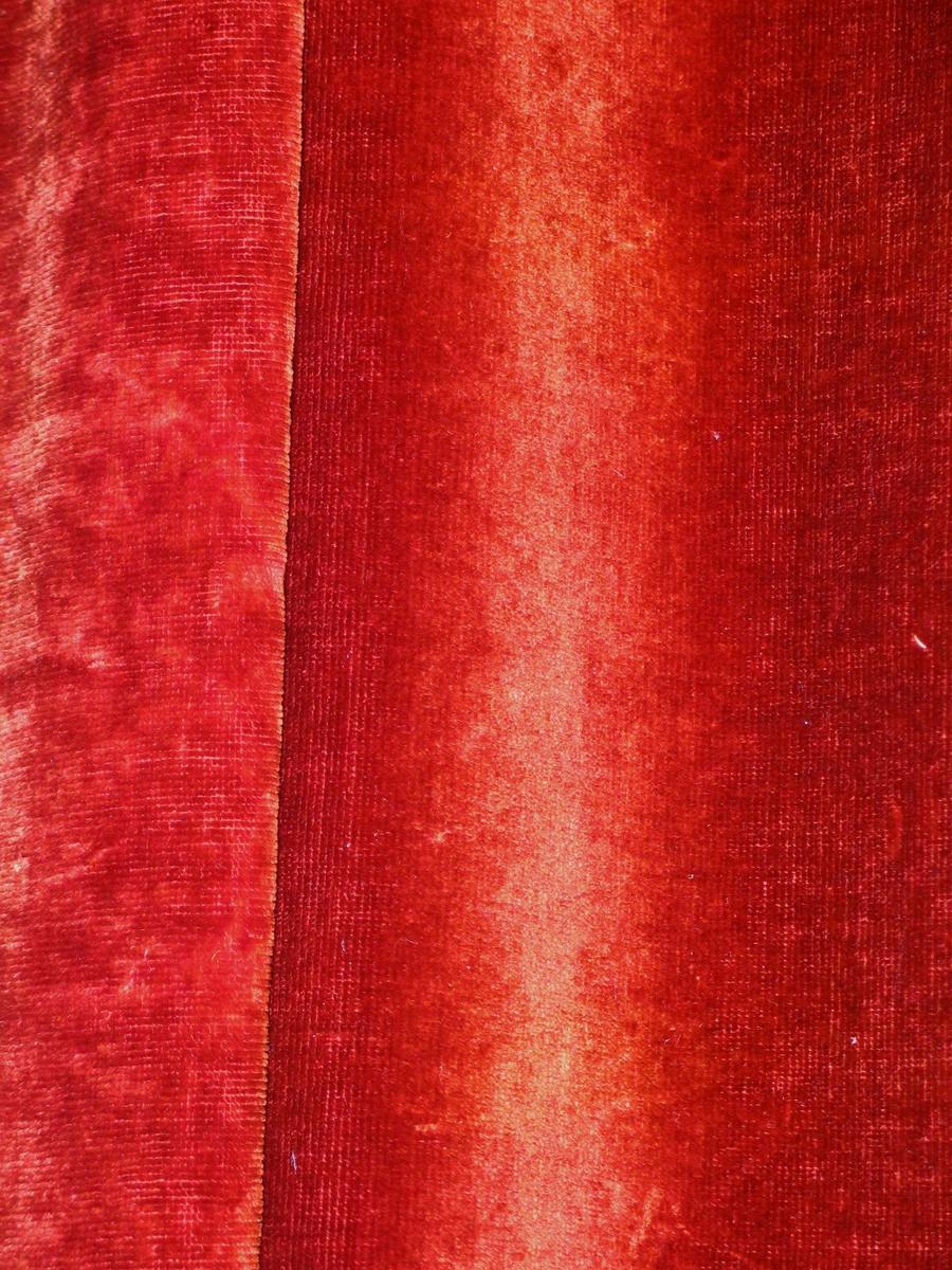 Rødbrun portierekappe i bomullsplysj. Plysj på begge sider. Isydd metallringer samtidig med en liten fold. Hengt på kroker i en trelist