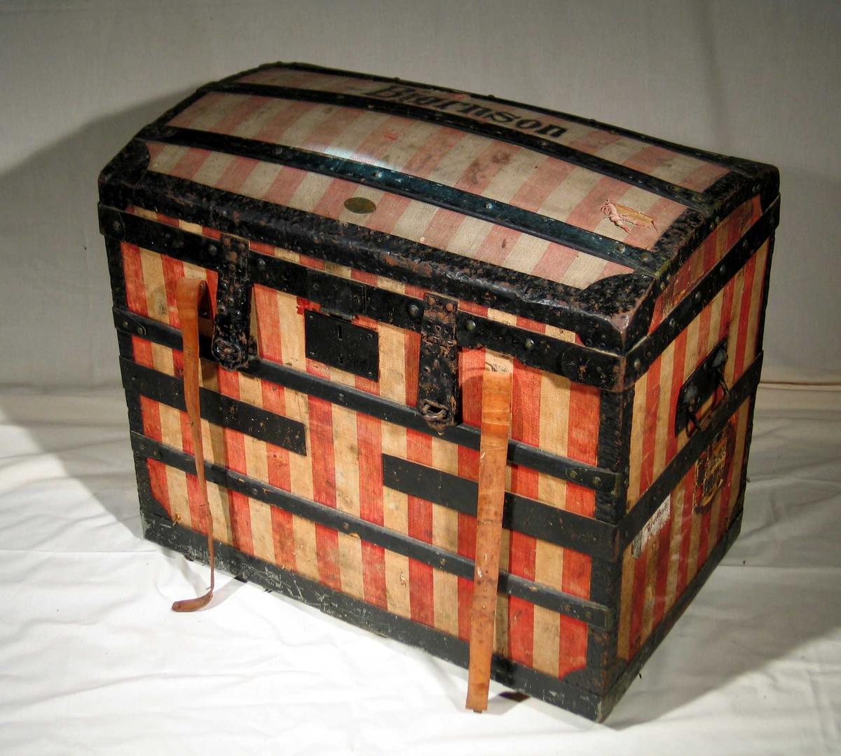 Høy kiste i tre trukket med rødt og hvitt kraftig stoff. Den har svartmalte jernbeslag og buet lokk. Innvendig er det tilpasset to kasser i tre med håndtak. Kisten er trukket med stripet papir. Skinnremmer og stort firkantet låsbeslag i front. Kisten har vært låst med to hengelåser. Svartmalte jernhåndtak på kortsidene.
