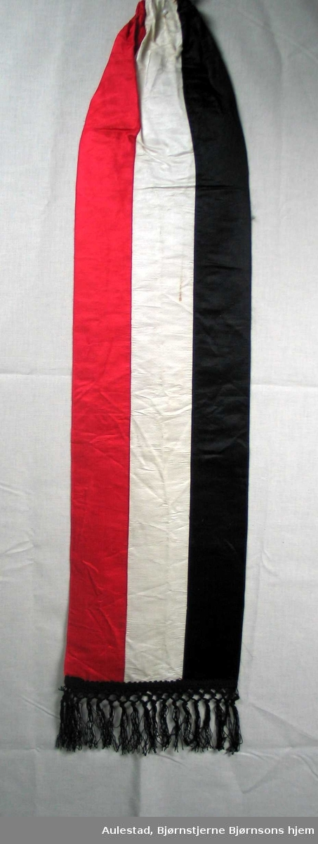 Begravelsessløyfe i svart, hvit og rød silke med svarte frynser. Ingen tekst.