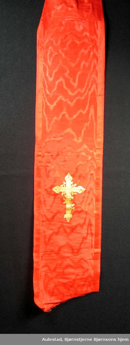 Begravelsessløyfe i rød silke med gullkors. Ingen tekst.