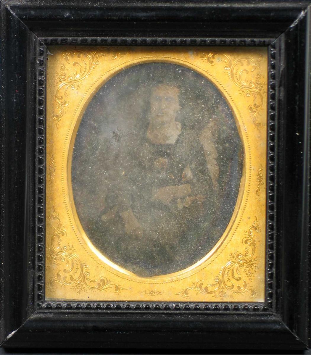 Bildet har en gyllen mønstret omramming, glass og svart treramme med perlekant. Motivet er svært utydelig.