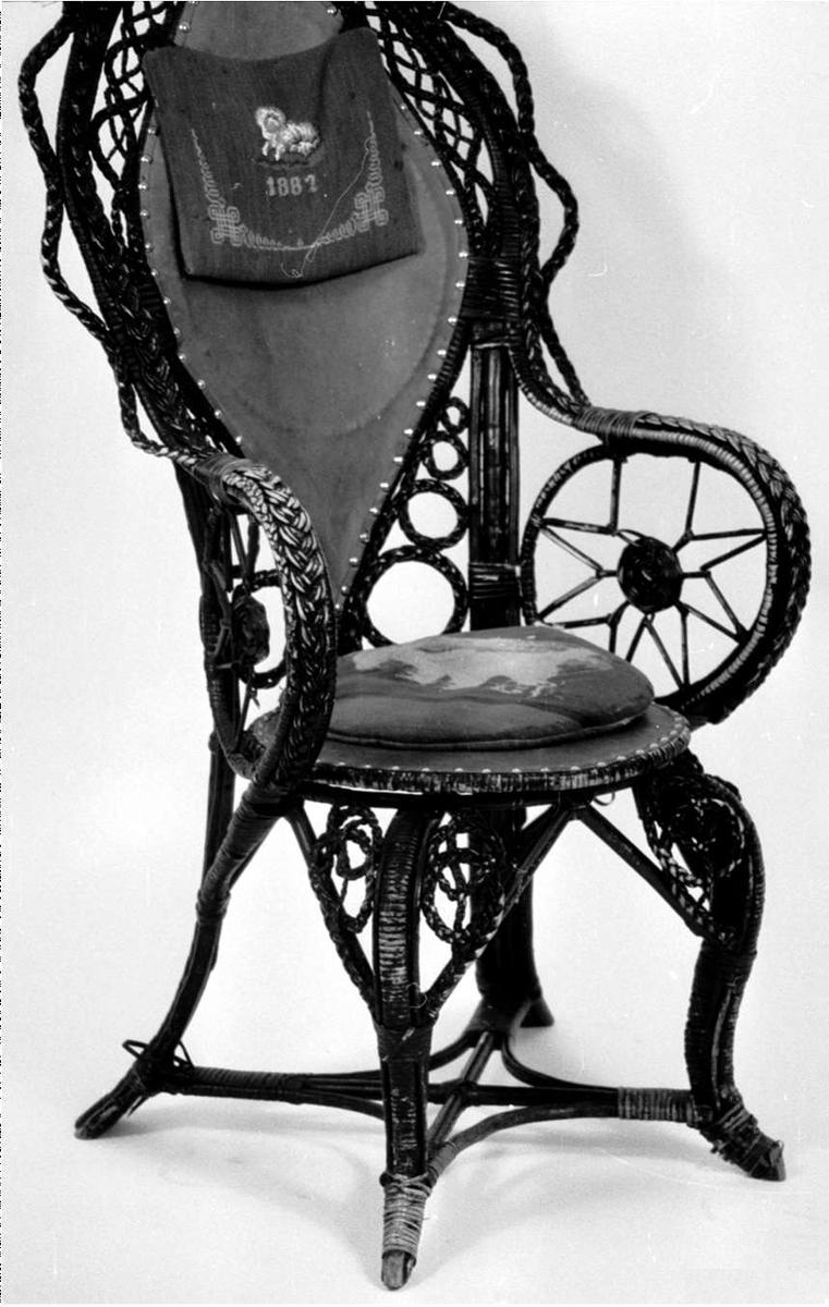 Høyrygget kurvstol med armlener i bambus. Sete og rygg er i lær. Det er festet en grønn pute i tekstil på ryggen og det er en løs grønn pute i tekstil til setet.  Putene er bordert med hund og årstall som motiv. Broderiene på puten på ryggen inneholder også perler.