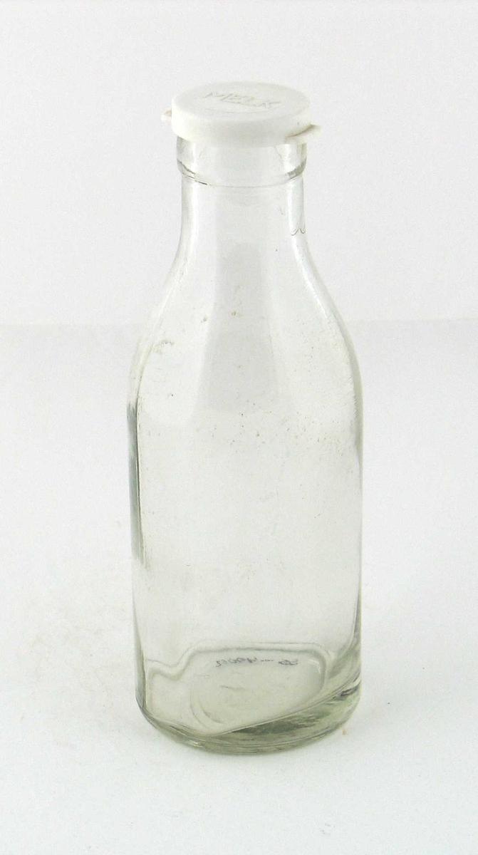 Melkeflaske av klart glass, hvit plastkork med innskrift: MELK.