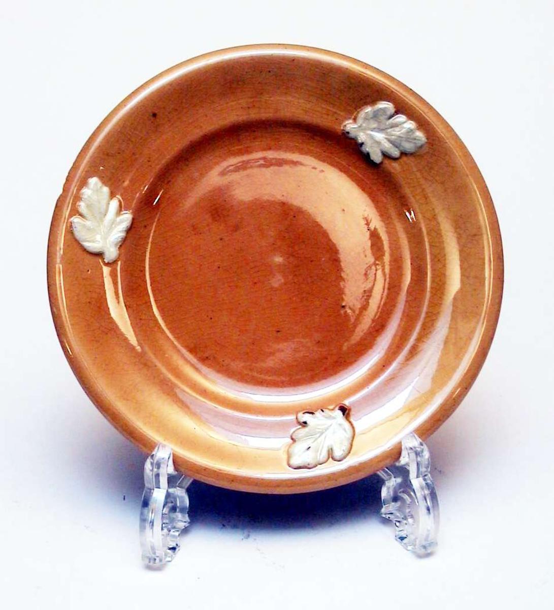 Gul asjett som er dekorert med tre påsatte, elfenbensfargete blader. Det er slått skår av asjetten. Asjetten har ingen produksjonsmerker.