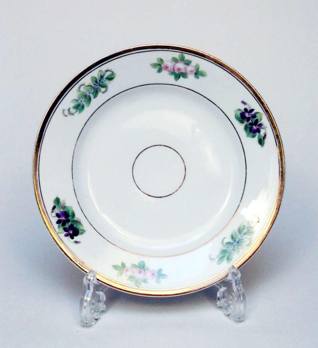 Asjett i hvit porselen med polykrom blomsterdekor og gullkant.