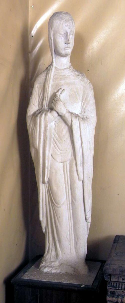 En avstøpning i gips av en treskulptur av jomfru Maria. Skulpturen sår på en sokkel kledd med tre.