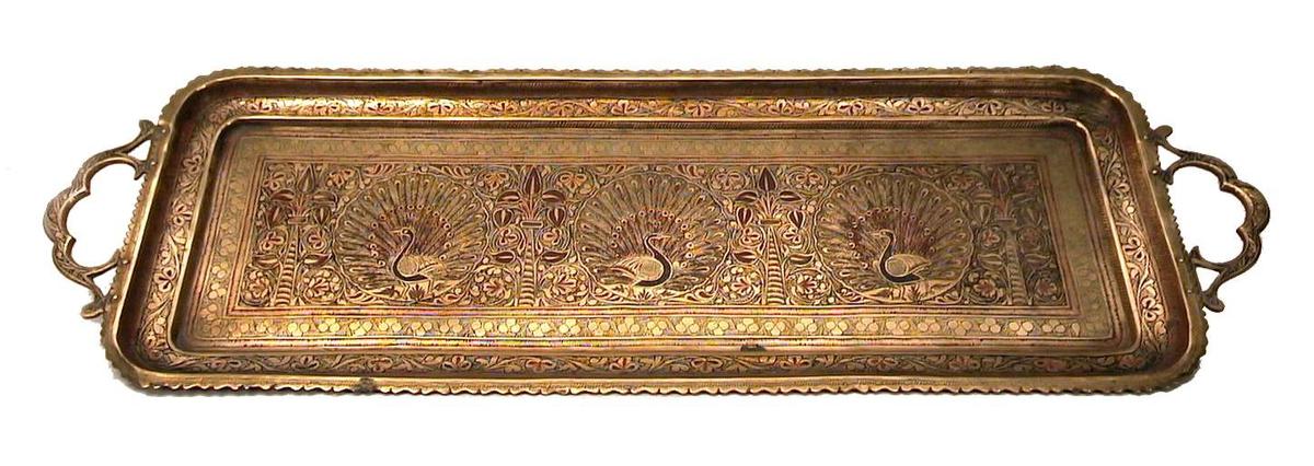Brett i messing og emalje. Brettet er rikt dekorert, bl.a. med påfugler. Dekoren gir brettet et orientalsk utseende.
