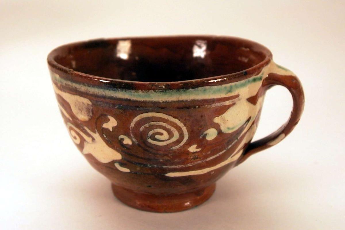 Grovt laget kopp i brunt leirgods med 'meksikansk' dekor.