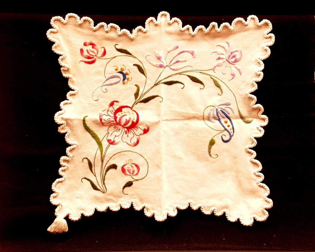 Brikke av benhvit, korskypertvevd bomull. Tunget kant med påsydde grove silkesnorer som ender i dusk i det ene hjørnet. Motiv: Asymmetrisk jugendmotiv - blomster og blad i plattsøm og kontursting.