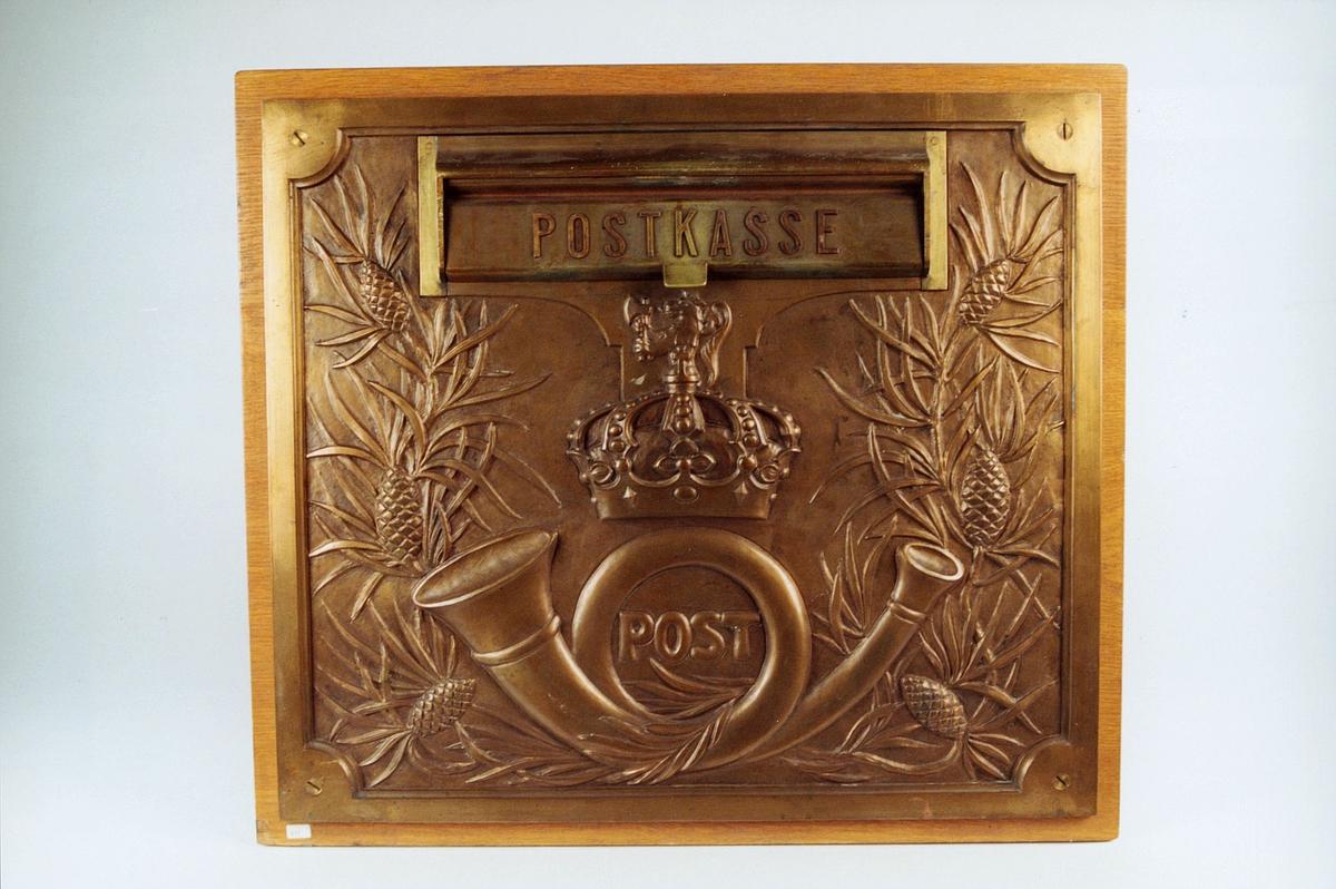 Postmuseet, gjenstander, postkasse, brevkasse, postinnkast, posthorn med krone og riksløve (postlogo) og Postkasse og Post, fronten er dekorert med barnåler og kongler.
