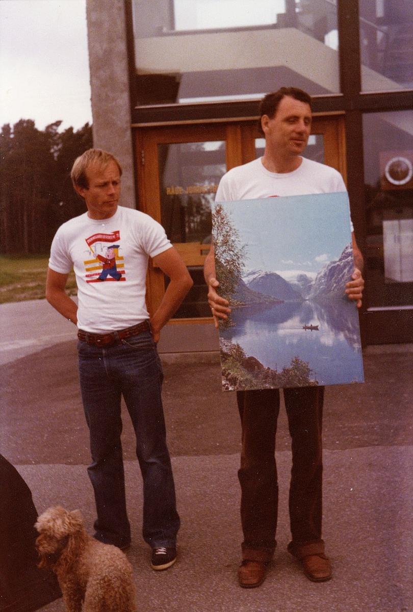 markedsseksjonen, mann holder maleri, bygningsarbeiderdagene'79, 1600 Fredrikstad, eksteriør, 2 menn