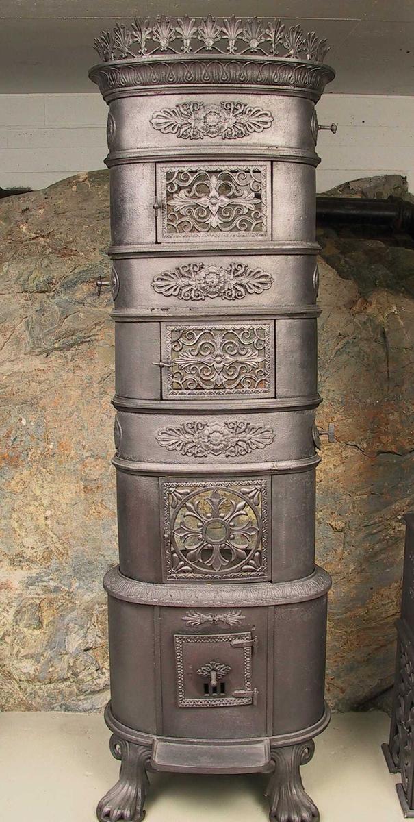 Deler til 2 etasjeovner  Næs Verk omkr. 1850-60.  Senklassisisme,  ovalt  Deler til 2 etasjeovner, Næs Verk omkr. 1850-60.  Senklassisisme, ovalt understell og tromler.  2 understell, det ene for hjørne (3 føtter, frontilegg),  det andre for rett vegg (4 føtter, sidefyrt) med  tilsvarende fyrkasser. På fyrkassens bakplate  verksnavnet Næs med skriveskrift på liggende plastisk  liten oval. Ovale tromler med rosetter og palmetter  som midtmotiv, rosetter/feieluker som kortsidemotiv.  4 tromler. 6 stk. mellometasjebøyler som gir nok  til 3 stk. mellometasjer. 2 gitterdører liggende  rektangelform, hører til de 6 bøylene. 2 bøyler som  gir høyere mellometasjer, 4 tilsv. gitterdører.  1 øvre bekroningskrans, palmetter gjen ombrutt.  (andre deler: Smia, Fjærkleiv)  Tilst. 1978 gamle skader, reparer m. jernblikk.