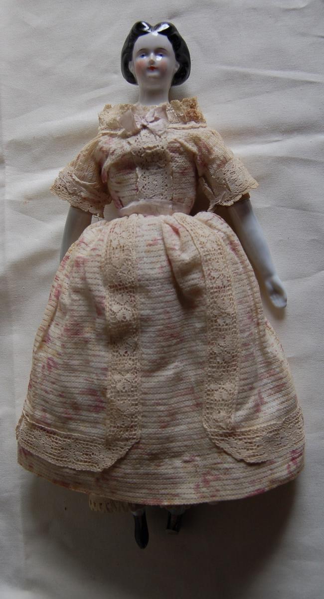 Kropp av tøy, hode og armer av glass. Hår og sko malt sort. Blomstret kjole med silkebånd, sløyfe og blonder.
