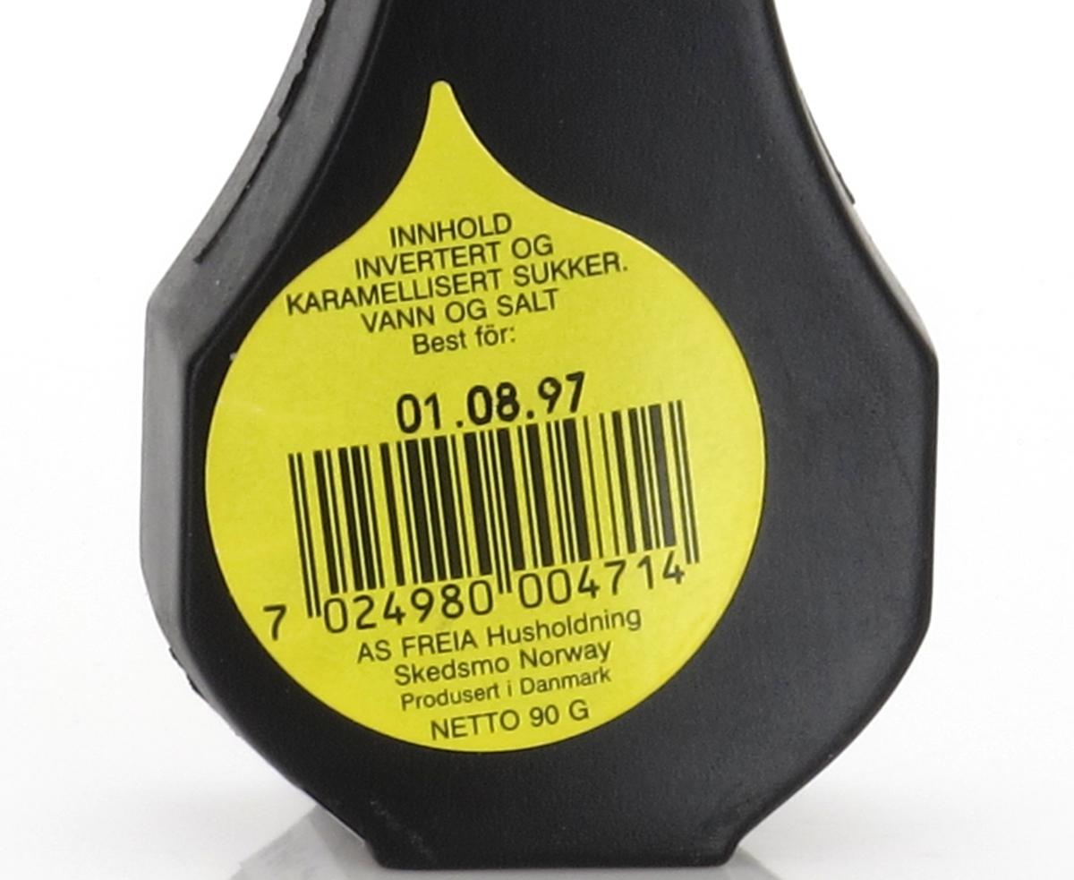 Liten plastflaske med skrukork, flasken er sort, korken gul.   Stempel fra  produsent i bunnen. Tilstand god.