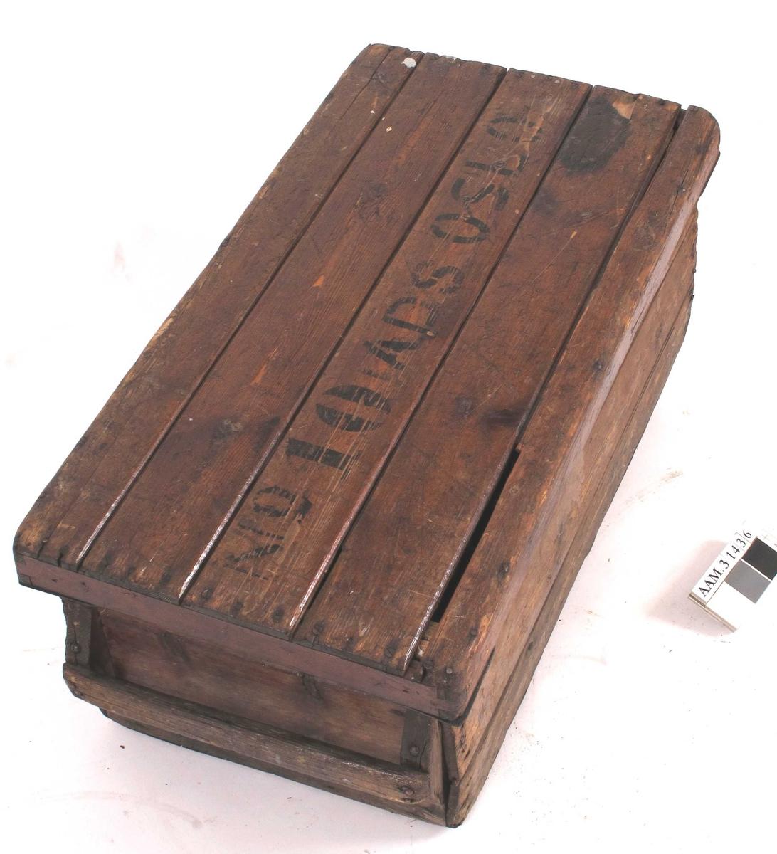 """Rektangulær trekasse med håndtak på begge kortsidene.  Både kasse og lokk er laget av bord som er spikret utenpå en svært enkel """"ramme"""".  Tre bord i høyden.  Bordene har not og fjær. Spor av lakk på utside og ubehandlet innside.    Løst lokk.  Lokket har vinkeljern skrudd på på undersiden av hjørnene.  Lokket består av fire bord av varierende bredde, trolig gjenbruk av panelbord med not og fjær, som ikke er forsøkt passet inn i hverandre.  Kassa bærer preg av å være hastig snekret sammen, og spikringen virker tilfeldig med svært varierende mengder spiker med nokså tilfeldig plassering, og ikke alltid helt rett slått inn.  Alle bordene er ikke like lange.  Lokket er mer forseggjort, og rammen er nøyaktig satt sammen og bearbeidet."""